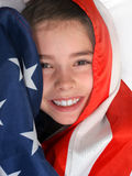 Patriotic Child. Young girl cloaked in the American Flag stock images