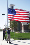 Patriotic Children. Two cub scouts participate in a flag raising ceremony Royalty Free Stock Image