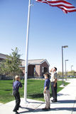 Patriotic Children. Two cub scouts participate in a flag raising ceremony with their den leader Stock Photos