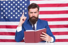 Patriotic concept. American lawyer teacher or tv host hold book american flag background. Love homeland. Man with beard. And mustache serious face with american royalty free stock photography