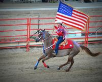 Patriotic Cowgirl on Horseback with Flag Stock Photography