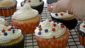 Patriotic Cupcakes. Placing American flag on decorated cupcake stock video