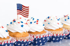 Patriotic cupcakes with sprinkles and American flag. Row of patriotic cupcakes decorated with sprinkles and American flag Royalty Free Stock Photo