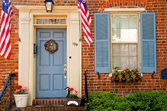 Patriotic doorway. Front entrance and doorway to an old, historic red brick building complete with American flags Royalty Free Stock Images