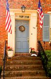 Patriotic doorway - vertical. Front entrance and doorway to an old, historic red brick building complete with American flags.  Chestertown, Maryland.  Suitable Stock Images