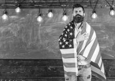 Patriotic education concept. American teacher covered with american flag. Man with beard and mustache on serious face royalty free stock photo