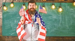 Patriotic education concept. Man with beard and mustache on happy face holds flags of USA, in classroom, chalkboard on royalty free stock photos