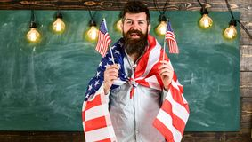 Patriotic education concept. Portrait of cheerful glad excited confident with toothy beaming smile student wearing denim. Casual outfit holding flag, chalkboard Stock Photography