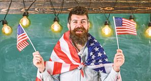 Patriotic education concept. Student exchange program. Man with beard and mustache on happy face holds flags of USA, in stock image