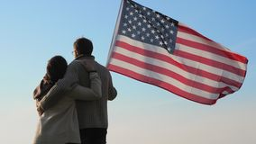 Patriotic family with a large flag of America in hand outdoors. A man and a woman are embracing holding large flag of America in their hands against a blue sky stock video footage