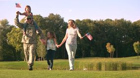 Patriotic family with military father. Walking soldier with wife and daughters with USA backgrounds stock video
