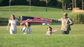 Patriotic family running with huge USA background outdoor. Soldier father. Lake in the park background stock video footage