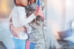 US flag being in hands of a nice little girl. Patriotic feelings. Close up of a US flag being in hands of a nice little girl while being on her mothers hands stock photos