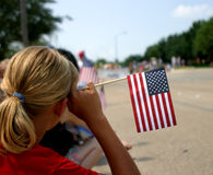Patriotic Girl. A girl shows her patriotism at a Fourth of July parade. Soft focus royalty free stock photo