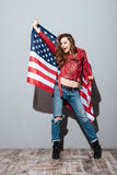 Patriotic girl wearing red leather jacket and holding USA flag Royalty Free Stock Photos