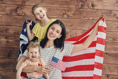 Patriotic holiday and happy family. Patriotic holiday. Happy family, mother and her daughter child girl with American flag at home. USA celebrate 4th of July Royalty Free Stock Photography