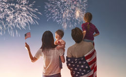 Patriotic holiday and happy family. Patriotic holiday. Happy family, parents and daughters children girls with American flag outdoors. USA celebrate 4th of July Stock Image