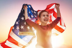 Patriotic holiday and happy kid. Patriotic holiday. Happy kid, cute little child girl with American flag. USA celebrate 4th of July Stock Images