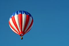 Patriotic Hot Air Balloon. A red, white, and blue hot air balloon soars in a clear blue sky Stock Image