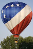 Patriotic Hot Air Balloon. A patriotic hot air balloon lifts off into the sky on a clear spring morning Stock Images