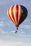 Patriotic Hot Air Balloon. American flag patriotic hot air balloon with American flag hanging beneath and floating through blue sky with clouds Stock Photo
