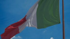 Patriotic Italian flag flying in wind against blue sky background, slow motion. Stock footage stock footage