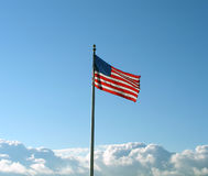 Patriotic Landscape. An American flag is flying in the wind as fluffy clouds compound around it royalty free stock photo