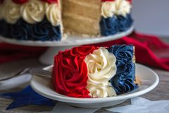 Patriotic Layer Cake Slice in Red White and Blue Rosettes. Patriotic layer cake slice in red, white and blue sitting on a white plate with the sliced cake in the Stock Photography