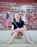 Patriotic Little Girl with Flag on Curb. Patriotic little girl sitting on curb against brick wall laughing with a US Flag in her hand Royalty Free Stock Photography