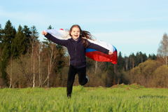 Patriotic little girl. Outdoor image of lovely patriotic little girl holding Russian flag over beautiful Russian nature Stock Images