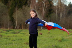 Patriotic little girl. Outdoor image of lovely patriotic little girl holding Russian flag over beautiful Russian nature Royalty Free Stock Image