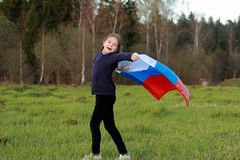 Patriotic little girl. Outdoor image of lovely patriotic little girl holding Russian flag over beautiful Russian nature Royalty Free Stock Images