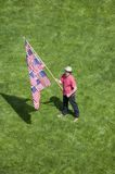 A patriotic man with a US Flag. Made of many US Flags stands alone in a green grass lawn at an anti-Iraq War protest march in Santa Barbara, California on March Royalty Free Stock Photo