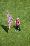 A patriotic man with a US Flag made of many US Flags stands alone in a green grass lawn at an anti-Iraq War protest march in Santa Stock Photo