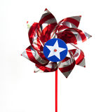 Patriotic Pin Wheel. Patriotic red white and blue shiny spinner wheel toy over white Stock Images