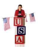 Patriotic Preteen. A happy preteen girl in patriotic colors waving 3 American flags while standing on giant alphabet blocks that spell USA.  Isolated on white Royalty Free Stock Image