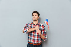 Patriotic proud young man standing and holding flag of USA Royalty Free Stock Image
