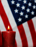 Patriotic Remembrance. One lighted red candle in front of a US or American flag.  A concept or symbol of patriotic remembrance of heroes and soldiers Royalty Free Stock Photo
