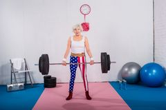 patriotic senior sportswoman lifting barbell and smiling stock images