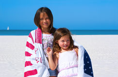 Patriotic sisters wrapped in American flag towel royalty free stock photo