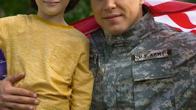 Patriotic soldier hugging his little son wrapped in US flag, peace for family. Stock footage stock footage