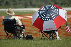 Patriotic spectators. Rear view of senior couple sat outdoors watching event, one under patriotic American umbrella Royalty Free Stock Image
