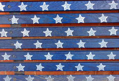 Patriotic stars and stripes. Bright blue and white stars and stripes painted across old wooden slats of a bench in the local park Stock Photography