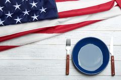 Patriotic table setting with USA flag on wooden background, flat lay. Space for text stock photo