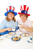 Patriotic Tea Party Voters. Patriotic conservative American voters sitting down to an actual tea party. White background royalty free stock photo