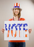 Patriotic teenager wearing American flag hat. Holding decorative vote sign Royalty Free Stock Photography