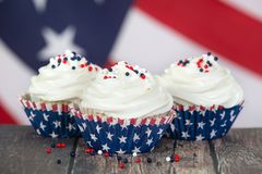 Patriotic 4th of July cupcakes. Patriotic 4th of July or Memorial Day celebration cupcakes. The American flag in the background Royalty Free Stock Photos