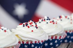 Patriotic 4th of July or Memorial Day cupcakes. Patriotic 4th of July or Memorial Day celebration cupcakes, close-up. The American flag in the background stock photos