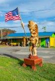Patriotic Tiki. Hawaiian Tiki holding American flag Stock Photos