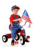 Patriotic Triker. A two-year-old waving an American flag while riding a trike and wearing a stars-and-stripes baseball cap.  Isolated on white Royalty Free Stock Images